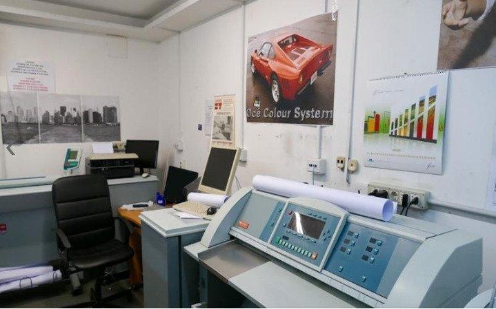 una stampante e dei monitor con, una scrivania e una sedia da ufficio nera