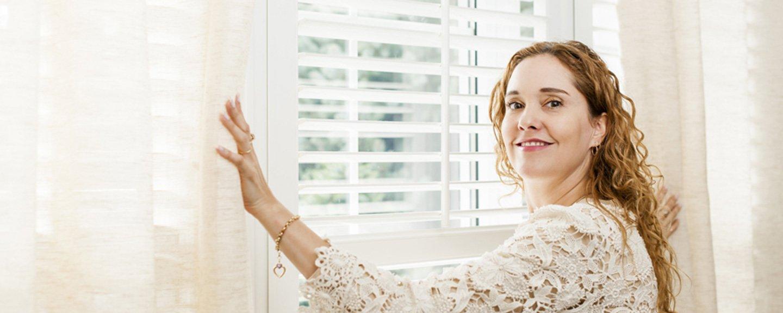 donna apre le tende di una finestra
