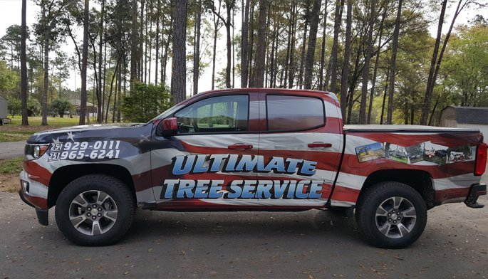 Tree trimming truck with vehicle wrap advertisment
