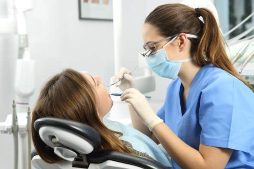 Dentista che esamina i denti pazienti con una sonda dentale e uno specchio in una scatola clinica