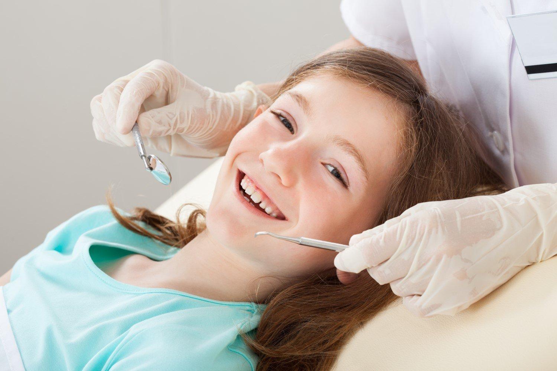 Primo piano bambina sorridente durante una visita dentistica