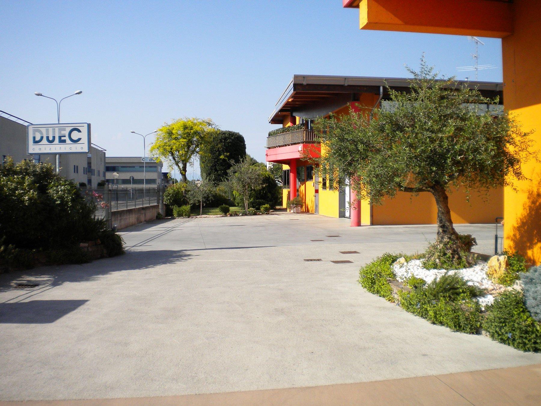 spazio all'esterno sulla destra un aiuola con delle piante e un albero, un muro giallo,sulla sinistra un cartello con scritto DUE C Colorificio e in lontananza degli alberi e una casa di color rosso e giallo