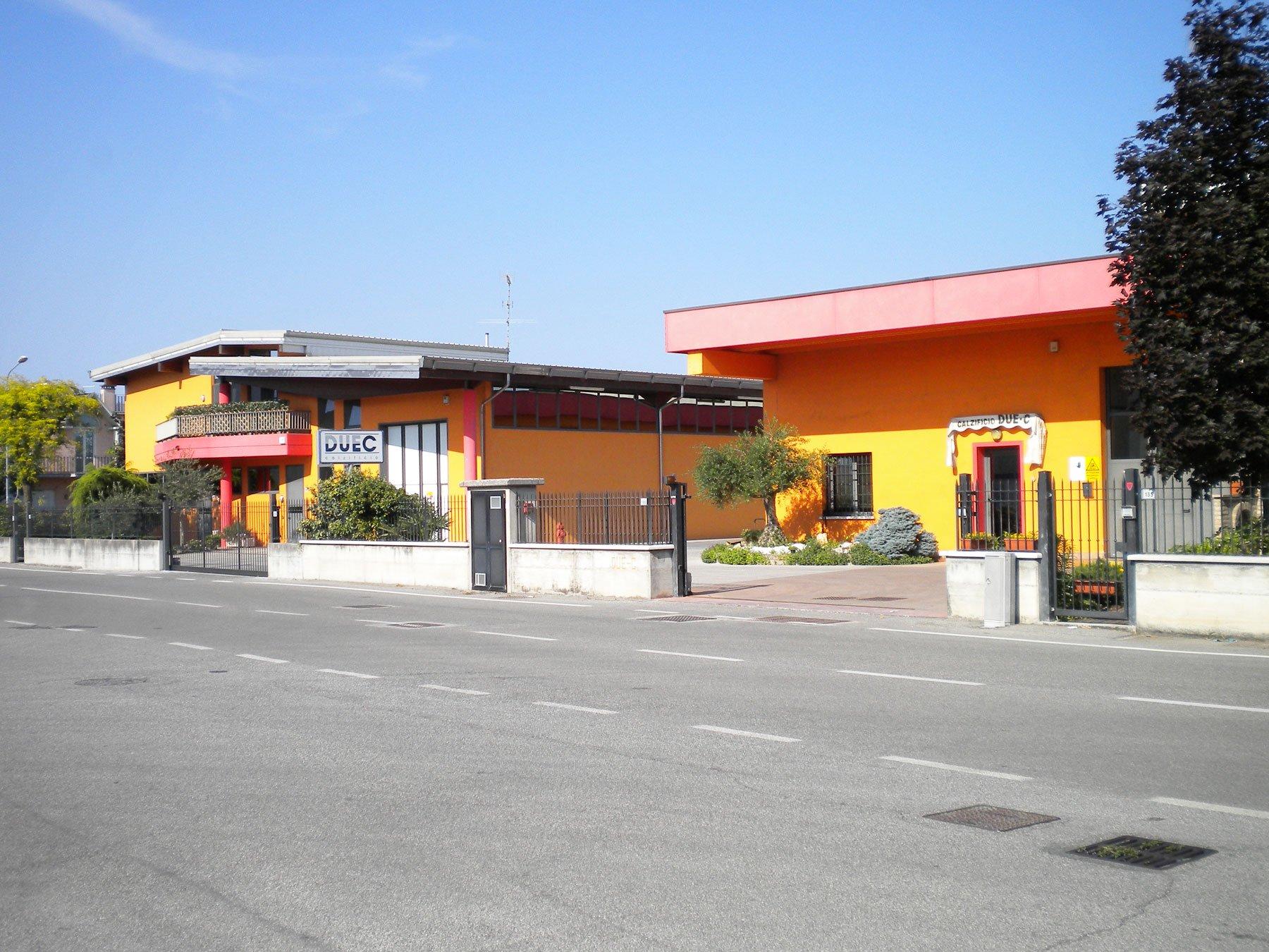 vista dall'altro lato del marciapiede di due stabili gialli e rossi con accanto delle aiuole con delle piante e degli alberi