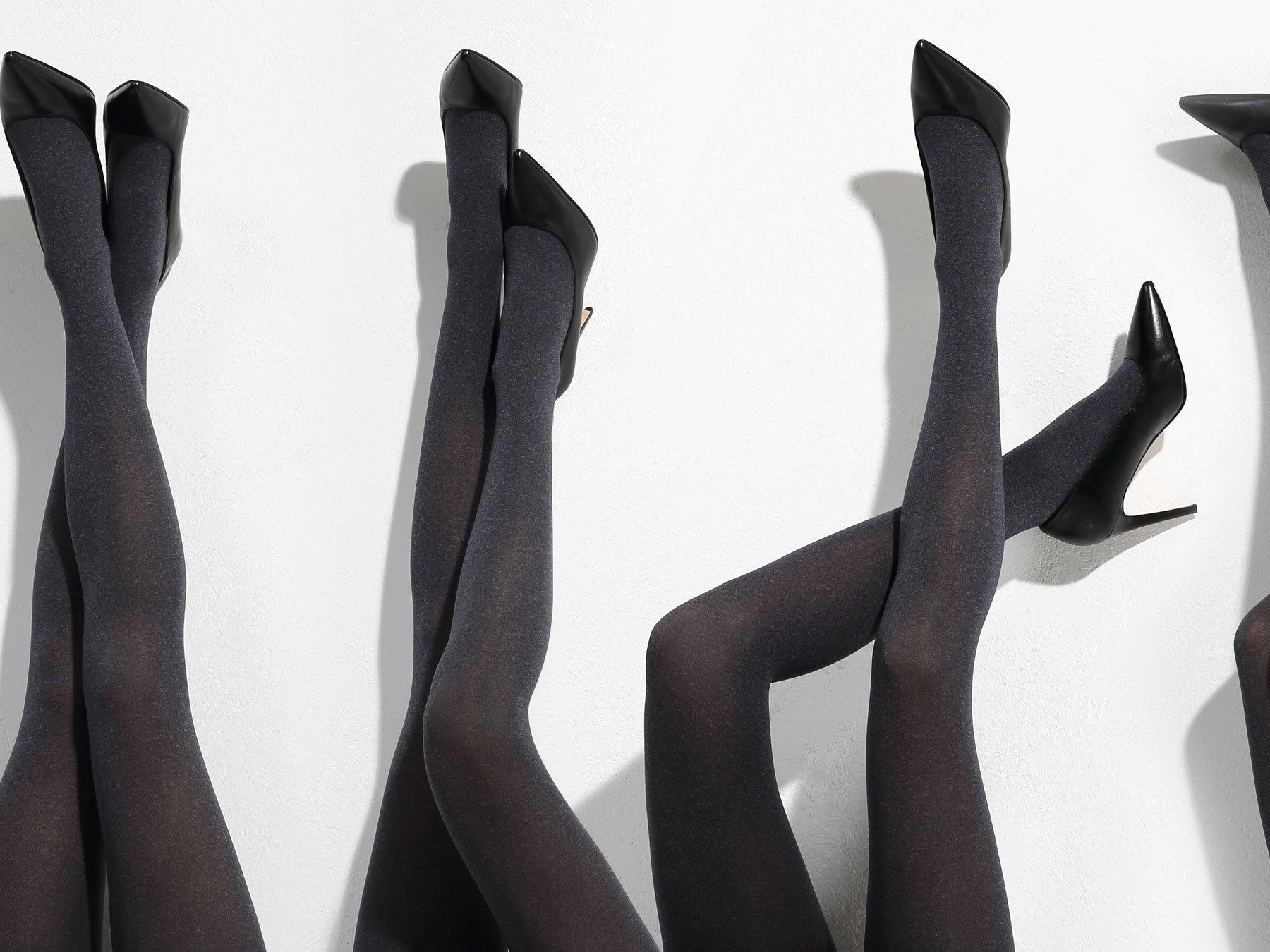 delle gambe di alcune donne con calze nere e scarpe con i tacchi di color nero