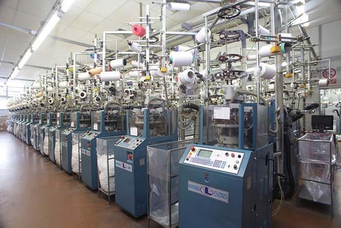 dei macchinari industriali di color blu e sopra dei rotoli colorati