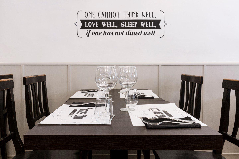un tavolo apparecchiato con una scritta sul mura in sfondo