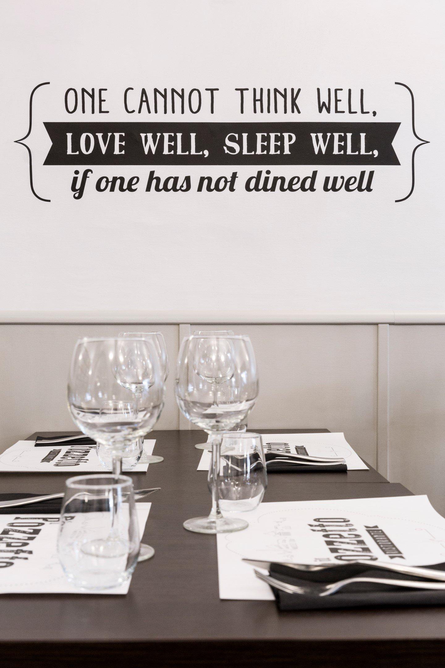 scritta sul muro con un tavoli in primo piano