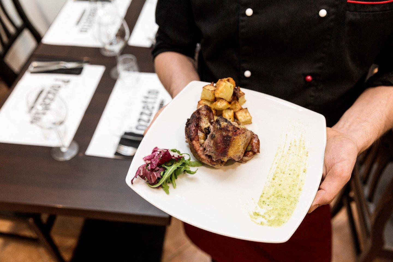 un piatto di carne retto dal cuoco