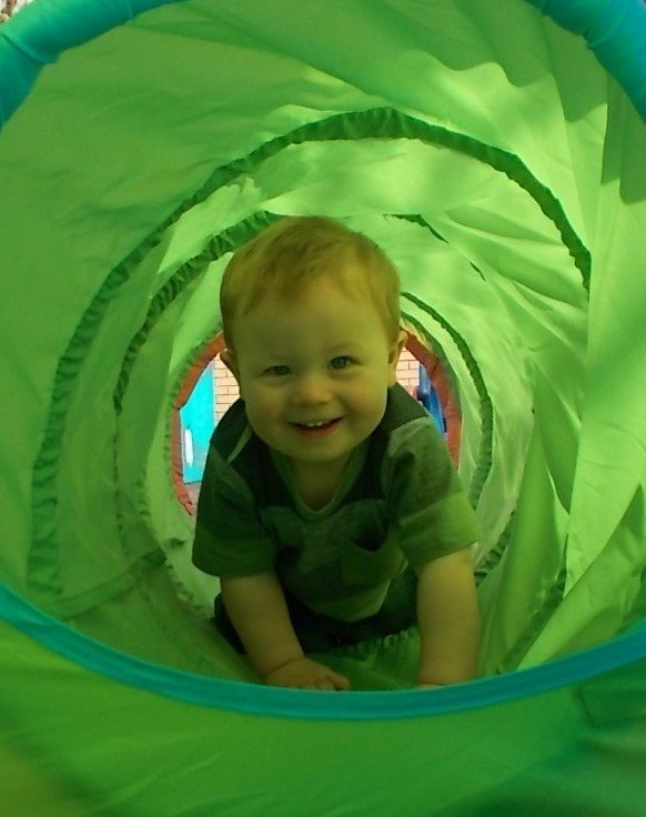 baby playing inside tube