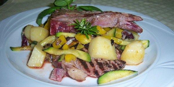 Piatto di carne con patate peperoni e zucchine