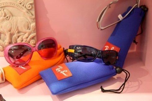 tre paia di occhiali da sole Rayban di color rosa, nero e uno bianco sopra a delle custodie