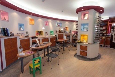 interno di un'ottica con pannelli con occhiali esposti e dei mobili con dei cassetti