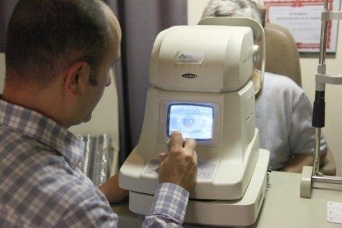 un uomo mentre utilizza un apparecchio elettronico per visite ottiche specialistiche