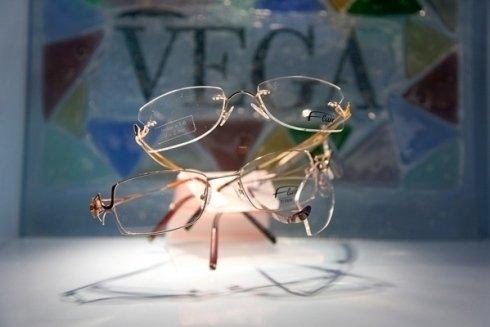 due paia di occhiali da vista  e dietro uno sfondo a mosaico con la scritta Vega