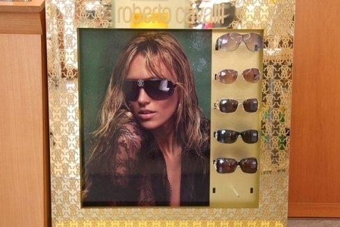 un pannello con l'immagine di una donna con degli occhiali da sole delle marca Roberto Cavalli e accanto degli occhiali esposte