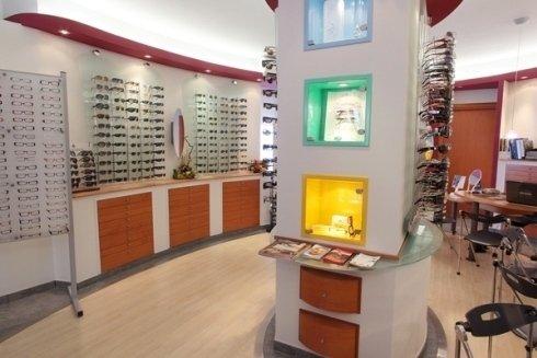 vista ravvicinata dell'interno dell'ottica con degli occhiali esposti su dei pannelli