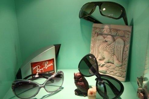 degli occhiali da sole Rayban di diversi colori,una statuetta di un gufo bordeaux e un rilievo di ceramica con un aquila disegnata