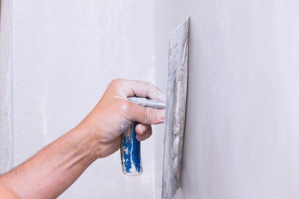 mano che usa una spatola per stendere stucchi