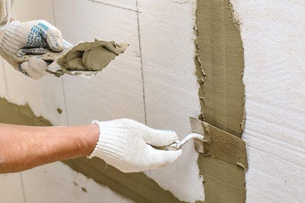 operaio munito di guanti e spatola mentre stende il cemento