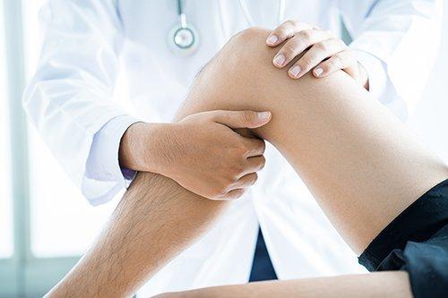 medico esegue manovra su ginocchio paziente