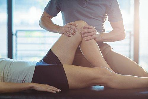 fisioterapista massaggia ginocchio paziente