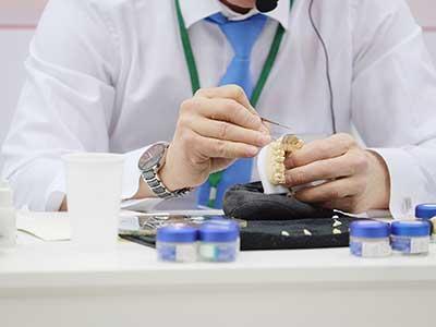 due mani di un odontotecnico al lavoro su una protesi dentale