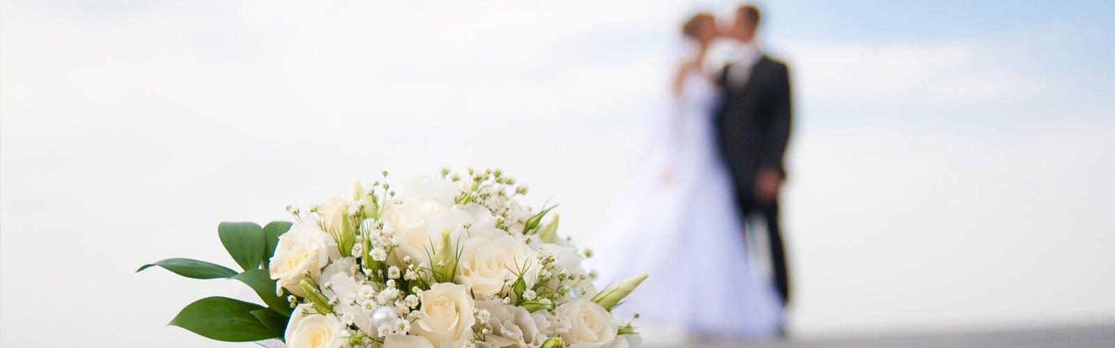 Vista ravvicinata di un mazzo di fiori bianchi e in fondo due sposi mentre si baciano