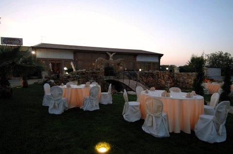 Dei tavoli apparecchiati all'esterno in giardino