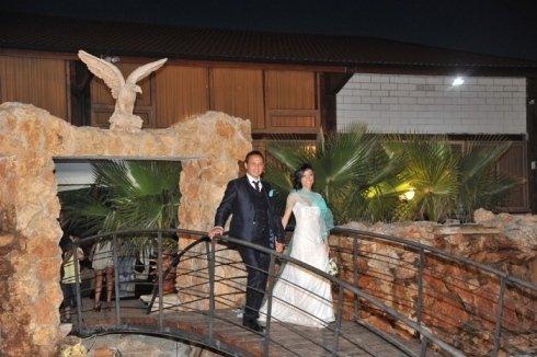 Una coppia mentre sorride su un ponte e vista di un arco e una statuetta di un uccello