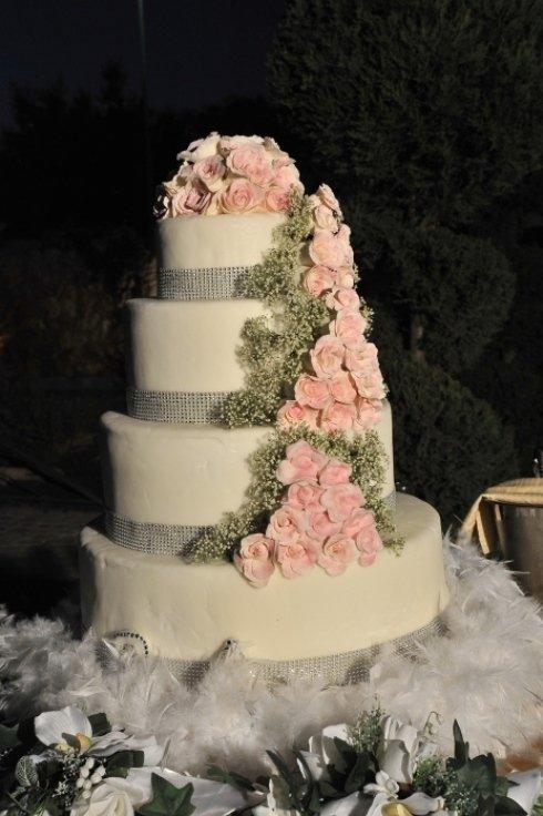 Una torta nuziale con decorazione di fiori di color rosa
