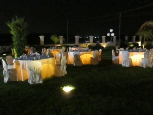 Delle tavolate apparecchiate con tovaglie bianche e gialle all'esterno