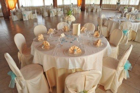 Delle tavolate apparecchiate con tovaglie beige e decorate con fiocchi azzurri