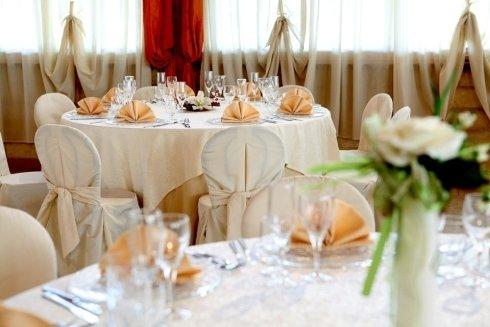 Delle tavolate apparecchiate con tovaglie beige, piatti e bicchieri