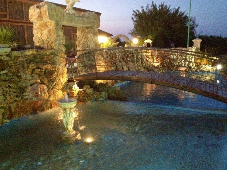Un ponte sopra una fontana con delle luci accese