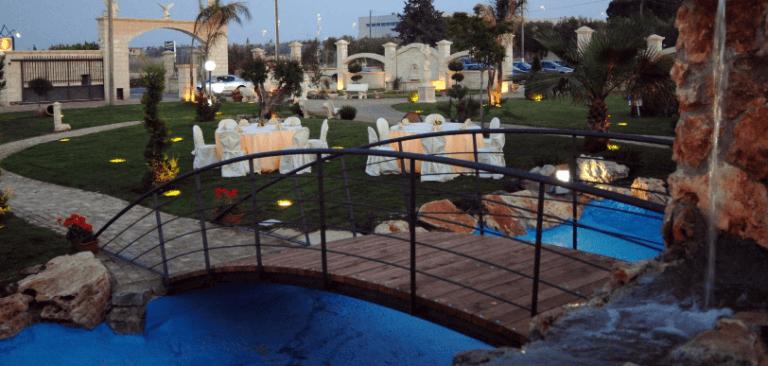Un ponticello sopra a una fontana e vista dei tavoli apparecchiati durante un evento serale