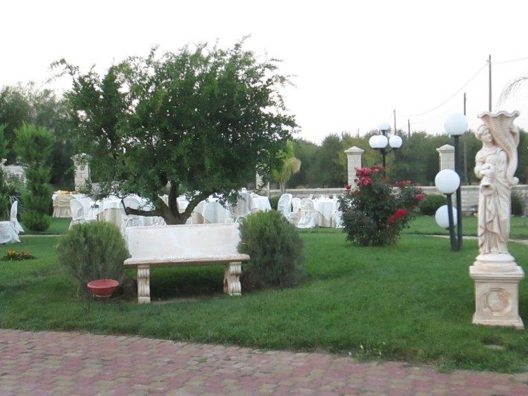 Una panchina, dei tavoli apparecchiati e vista del prato e dei lampioni