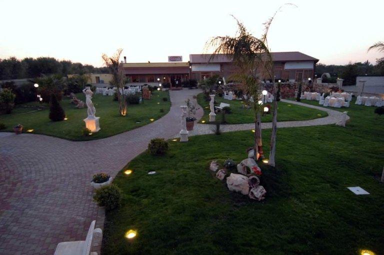 Una villa con davanti prato ampio con dei tavoli apparecchiati e luci accese