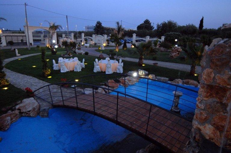Una fontana e vista di tavoli e sedie durante un evento serale