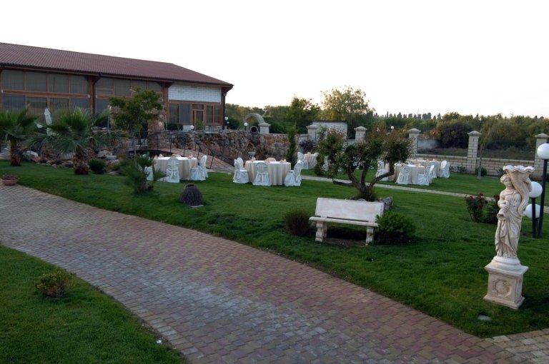 Una camminata e sulla destra un prato verde con tavoli e sedie