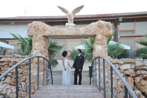 Una coppia mentre si tiene le mani sotto a un arco in rocce e una statuetta di un uccello