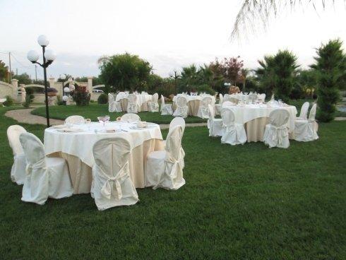 Dei tavoli con tovaglie bianche e delle sedie con coprisedie di colore bianco