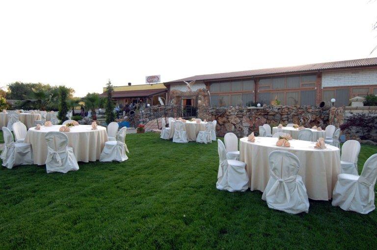 Dei tavoli rotondi con tovaglie beige, tovaglioli di color pesca e delle sedie con copri sedie di colore bianco