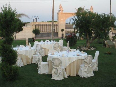Dei tavoli in un prato e a distanza vista di un' entrata