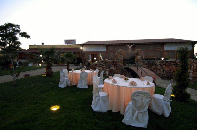Una villa e dei tavoli davanti durante la sera