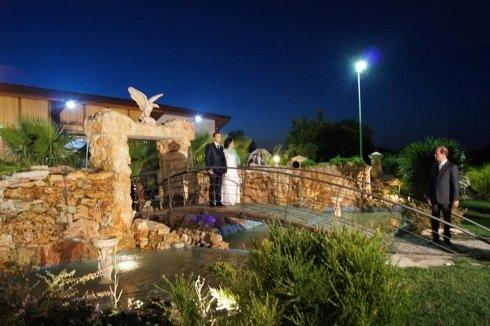 Una coppia in posa su un ponte sopra a una fontana