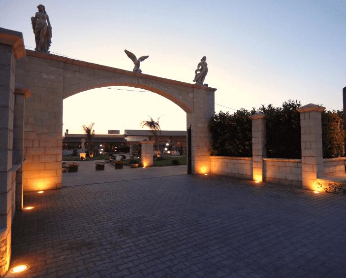 Vista di una entrata grande di una villa con delle luci accese, delle statuette e sopra un'arcata
