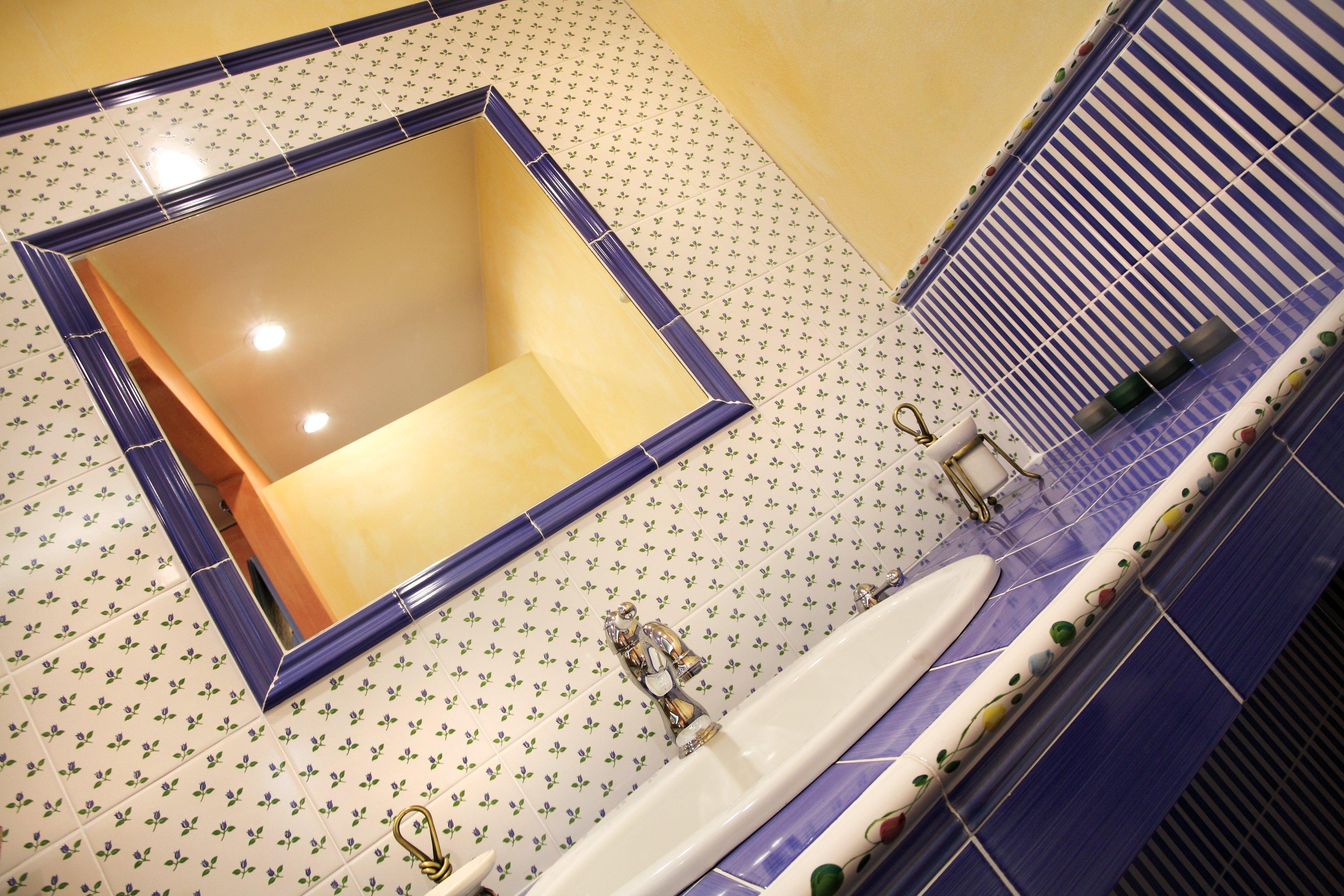 Foto laterale di un bagno con pareti gialle e blu scuro.