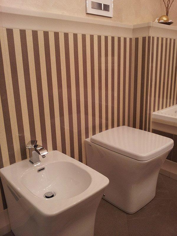 Bidet e bagno con parete a strisce verticali.
