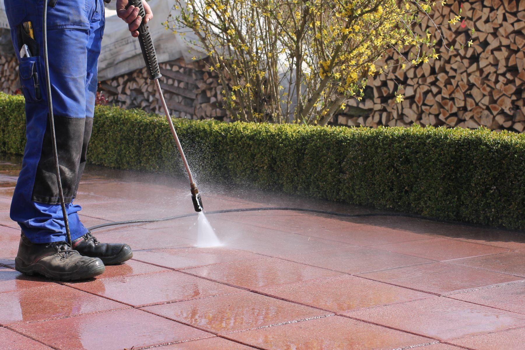 un uomo che pulisce un pavimento esterno con un'idropulitrice