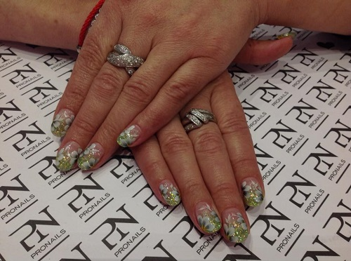 delle mani con delle unghie con dei fiori bianchi con foglie verdi